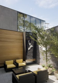 An internal courtyard features Boxwood chairs and coffee table by Janus et Cie.
