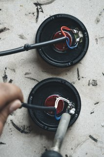 Attach Wires: The positive and negative cables are connected to the drivers with a soldering iron. The red wire marks the left ear, the white the right. With the cables attached, each channel can be individually tested for sound quality.