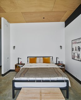 In the master bedroom, the steel bed from Room & Board is framed by two nightstands from West Elm.