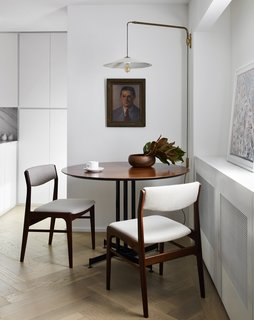 Kitterman designed built-ins along one wall of the apartment to hide heating and <br>cooling equipment. The pendant light, dining table, and chairs are all vintage, sourced from Europe and Palm Springs. Herringbone oak floors throughout are by LV Wood.