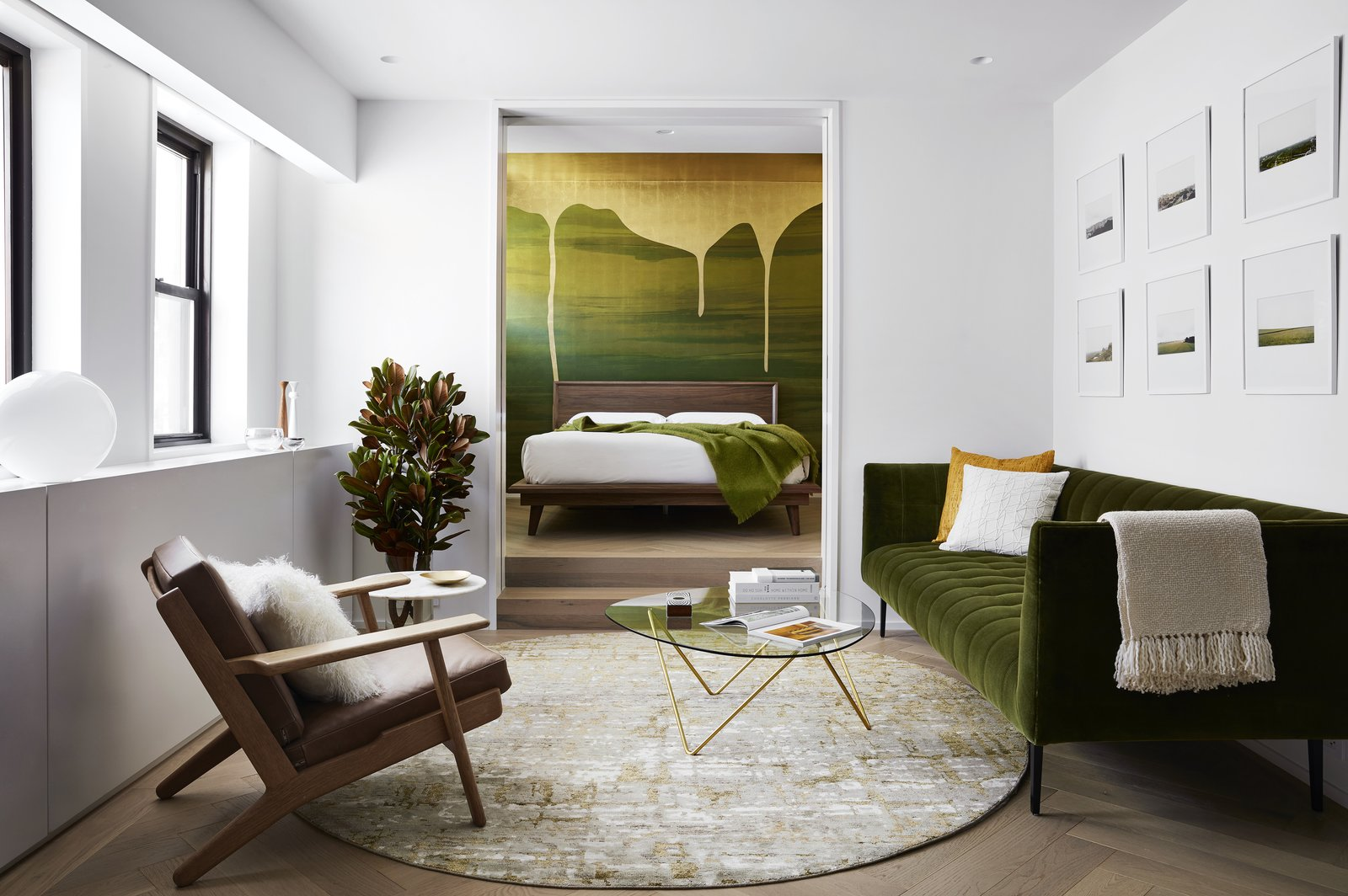 Stadt Architecture's Christopher Kitterman transformed a generic studio in Chelsea into a bright one-bedroom apartment for Vancouver couple Dale Steele and Dan Nguyen. The living room features a Hans Wegner GE290 lounge chair upholstered in leather by Spinneybeck, a round rug and Cobble Hill Adams sofa from ABC Carpet & Home, a Pedrera coffee table by Gubi, and a Bob side table by Poltrona Frau. An automated lift raises a TV from inside the custom millwork under the window. Acid-etched tempered glass doors lead to the bedroom.