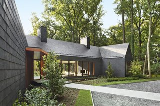 When Marlene and E. Dale Adkins's home of 22 years, a 1960s ranch house in Greenspring Valley, Maryland, was lost in a fire in 2013, the couple vowed to rebuild. Finished last year, their new home is covered in dark slate shingles for the sides and roof, Cor-Ten steel accents, and charred cedar for the gable fronts.