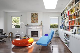 An off-center skylight brings natural light into the living room, where the existing fireplace was refinished in metallic paint. A fiberglass Koishi pouf by Naoto Fukasawa for Linea sits by an Eames sofa. The painting is by Vanessa Prager.