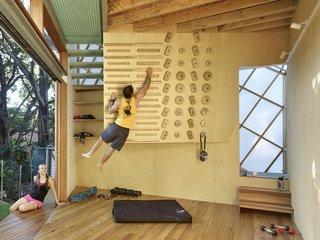 A climbing wall on the ground floor mimics the playful atmosphere of a children's tree house.