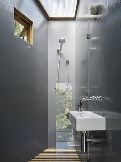 A skylight brings air and light into the bathroom. Because it is outfitted with amenities like plumbing, the tree house can also act as a self-contained dwelling.