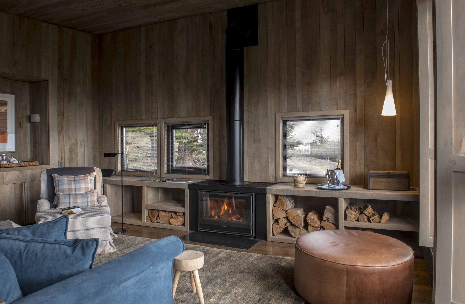 Living Room, Wood Burning Fireplace, Floor Lighting, Medium Hardwood Floor, Pendant Lighting, Rug Floor, Chair, and Sofa  Awasi Patagonia