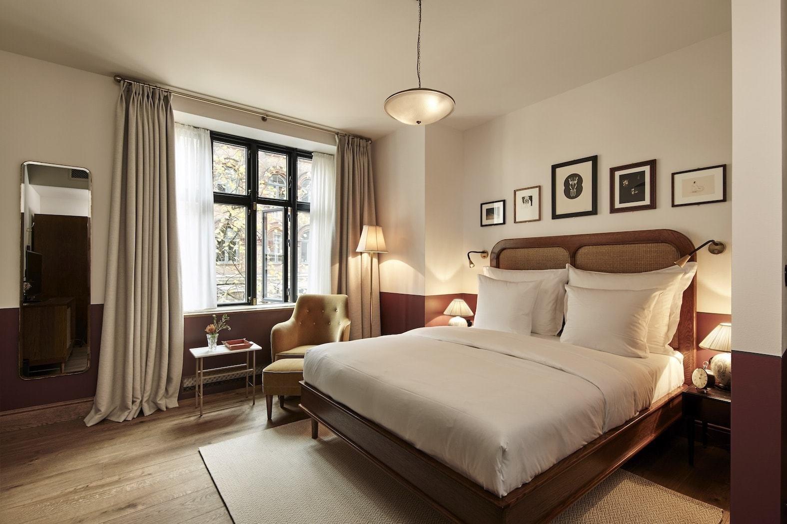 Bedroom, Table Lighting, Floor Lighting, Night Stands, Wall Lighting, Pendant Lighting, Medium Hardwood Floor, Chair, Rug Floor, and Bed  Hotel Sanders