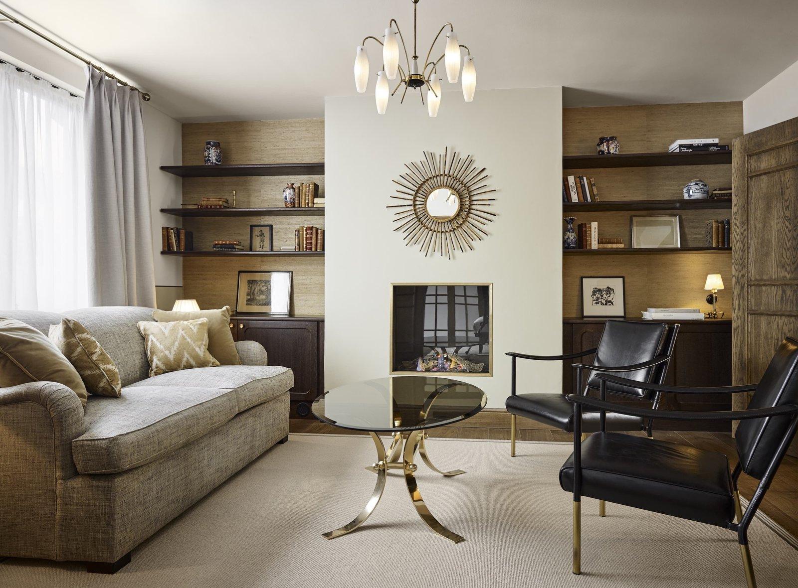 Living Room, Sofa, Shelves, Medium Hardwood Floor, Pendant Lighting, Table Lighting, Coffee Tables, Rug Floor, Chair, and Standard Layout Fireplace  Hotel Sanders