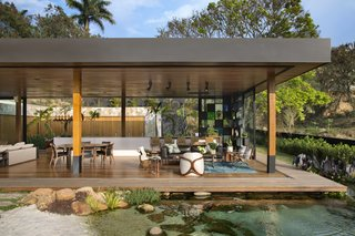Beyond the living room and deck, a natural pool filled with koi fish serves as a unique focal point for the tropical garden.