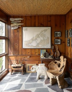 "The sunroom—or ""museum of natural history,"" as the couple call it—showcases an array of objects, including a massive chair carved from a single tree trunk and a terra cotta elephant used as a side table."