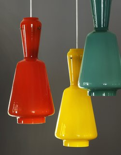 Colorful 1950s FontanaArte pendants hang over the dining room table.
