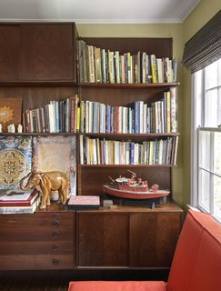 "In the library, a walnut shelving unit by Poul Cadovius faces a sofabed from CB2. Among the items on display is a motorized model fire boat built by Francine's late father. ""It's what you do when you're a retired engineer with time on your hands,"" Francine explains."