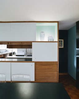 """In the dining room, the sliding-panel cedar cabinets feature a glass display case reminiscent <br>of the tokonoma found in traditional Japanese architecture, to which Girard professed a """"profound debt."""" In the kitchen, original pale orange Formica counters were replaced with crisp white ones."""