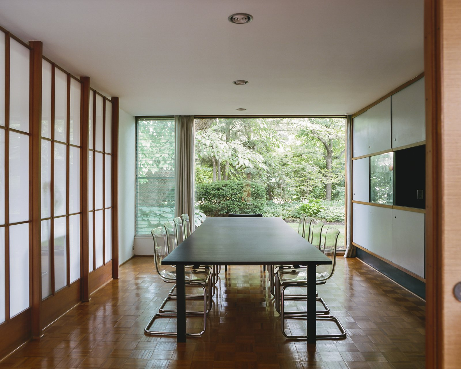 Dining Room, Table, Recessed Lighting, Medium Hardwood Floor, and Chair  Best Photos from This Michigan Couple Found Out They Own the Last Standing Home by Alexander Girard