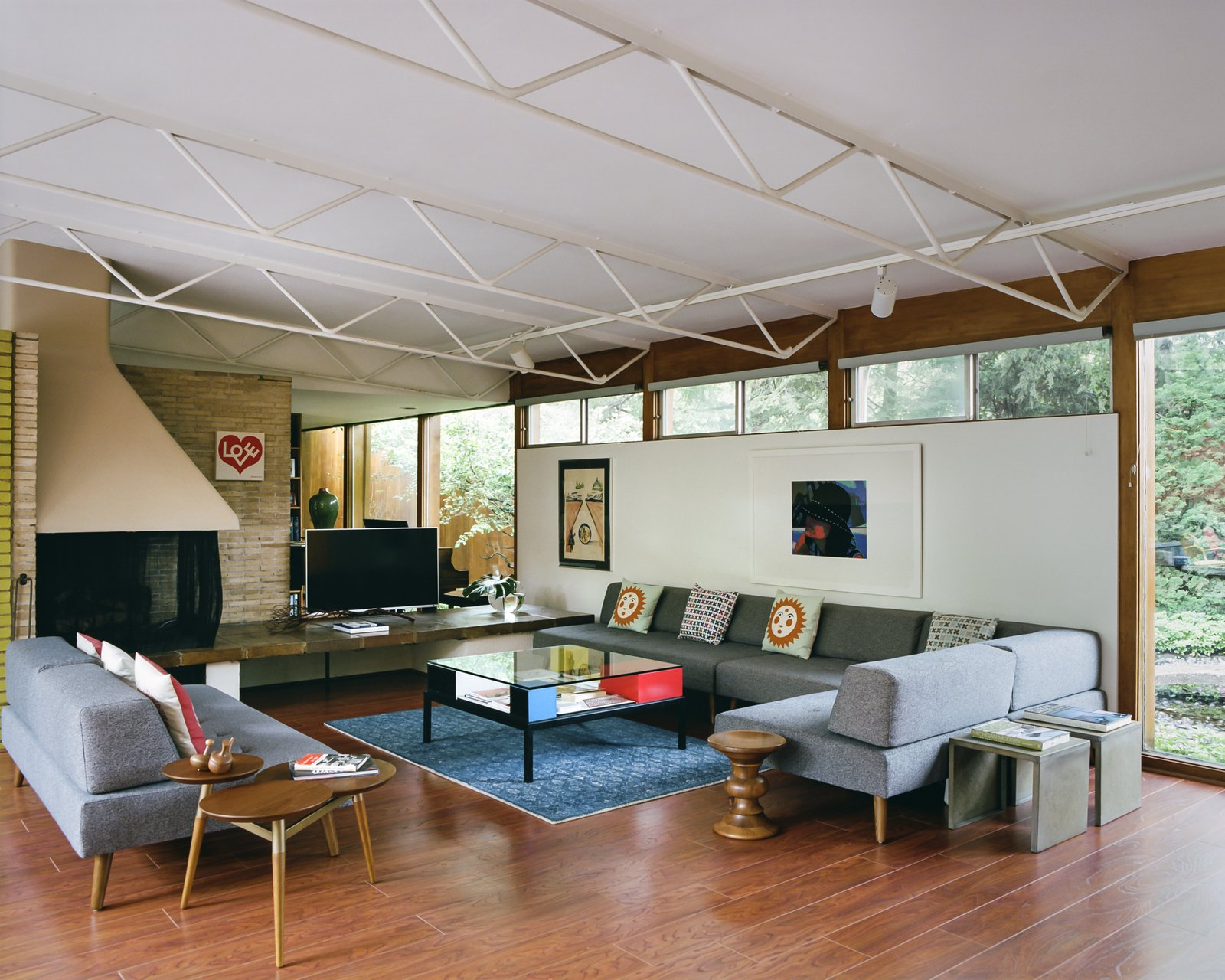Living, Corner, Coffee Tables, Track, Sofa, Medium Hardwood, Sectional, End Tables, and Rug  Living Medium Hardwood Rug Track Sectional Photos from This Michigan Couple Found Out They Own the Last Standing Home by Alexander Girard
