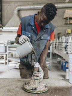 4. Cast the Mold: Before filling the mold, Mamadou uses two vessels to decant the concrete to help eliminate large air bubbles, then lets it sit until the remaining bubbles rise to the <br>surface. Then he slowly pours the mixture into the mold.