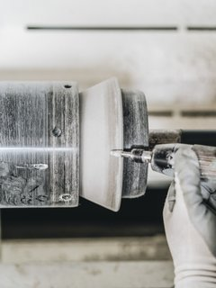 7. Smooth the Edges: The mold leaves a ragged edge of hardened cement paste at the top and bottom of the form. Artisan Buga Radu threads the pendant onto a lathe and hand-trims the rough edges with a die-grinder to create the bell edge.