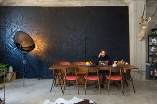 Rather than treating the concrete walls, Morrison hung a massive painting by her brother to give the dining room depth.