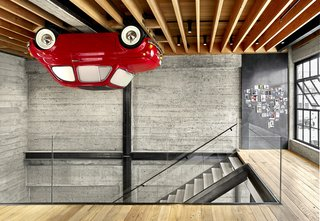 Vehicle Wall Art supplied the loft's most unusual feature, a 1965 Fiat Nuova 500 F mounted upside-down on the ceiling. Magnetic panels of blackened and waxed steel display smaller artworks. The floating stairs replaced a ramshackle set of steps.