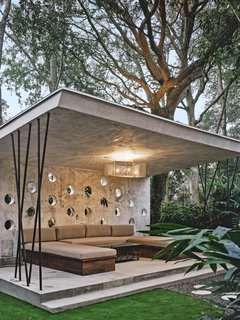 Hoertdoerfer's vision for the open-air cabana included holes in the wall for plants to poke through. Karen designed the seating and the chandelier, which was fabricated by artist Eric Doran from a piece of metal Karen found in his shop.