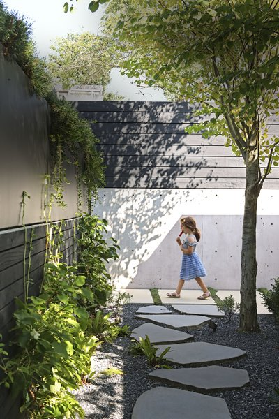 A black-stained Western red cedar fence now runs along the perimeter of Sharen McLean and Mark Derraugh's property in Vancouver, part of a complete revamping of the couple's outdoor space. The project was spearheaded by Sharen's daughter, Andrea McLean, whose daughters and nephew make the most of the urban oasis.
