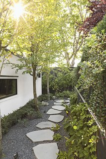 """Katsura trees, climbing hydrangeas, and basalt stepping stones create a pleasing passageway between the lower back deck and the new garage. """"What could have been leftover space, I wanted to be a promenade,"""" says Andrea."""