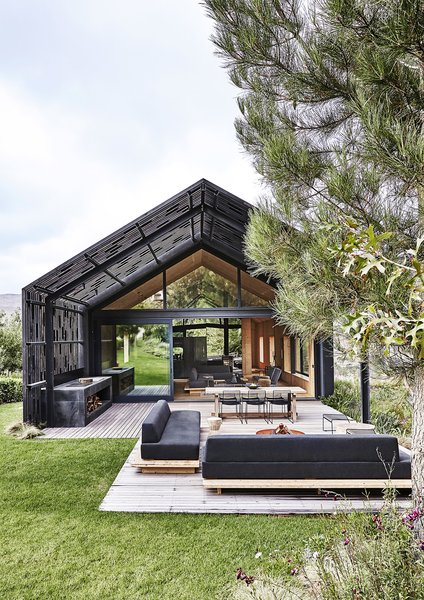 A blackened-timber pergola extends from the modern barn that architect Greg Scott designed for Jody and Deirdre Aufrichtig in the Elgin Valley, an apple- and grape-growing region near Cape Town. Made of narrow slats stabilized with randomly scattered blocks of wood, it  covers roughly half of the outdoor deck.