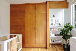 The nursery features mahogany cabinets and the crib is from Crate and Barrel.