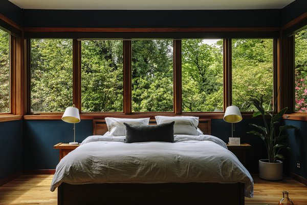 Windows offer wraparound views in the master bedroom. The nightstands and bed are from the Matera line by Sean Yoo for Design Within Reach; the Stem lamps are from Rejuvenation. The last owner painted the walls Gentleman's Gray by Benjamin Moore.