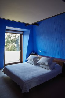 In a guestroom in Villa 1, an original 1970s bed by Fagnola is paired with a new Tab T lamp by Flos and Yves Klein blue walls.