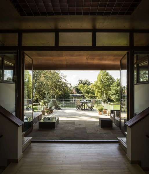 Atop the enclosed pool area, a limestone patio flows into the living room. In the yard, a small pavilion, which resembles a miniature version of the house, offers a place to sit and enjoy the gardens.