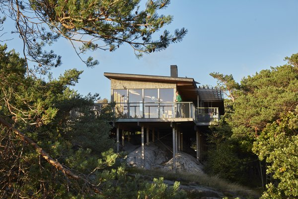 Tomas Haeger and Tina Linde's desire for simple weekend and  summer living led STEG Arkitekter to design a multi-volume retreat for the couple on the island of Tjörn. Clad in locally sourced fir, the house perches on pillars directly atop boulders that mark the steep site.