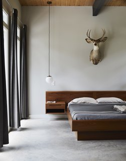 The master bedroom features a vintage Danish teak platform bed from Nordisk Andels-Eksport, a Globe pendant from West Elm, and drapes from IKEA. The mount was a gift from a friend.