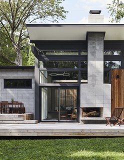 A double-sided fireplace shared with the living room warms the deck on cool evenings. Bob sited the house and strategically placed windows to take advantage of shade in summer and solar gain in winter. The outdoor seating is from IKEA.