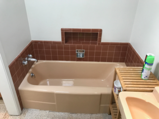 A Jack-and-Jill bathroom with worn fixtures and finishes was tweaked so that it solely connects to the principal bedroom and forms a private suite.