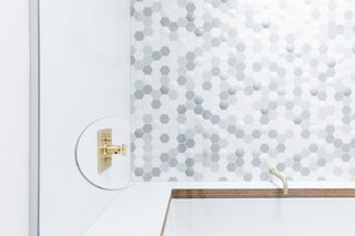 """A thoughtful cut-out in the glass enclosure allows people to reach the faucet without being sprayed by the shower. """"It's a bit of a signature for us,"""" Horner remarks."""