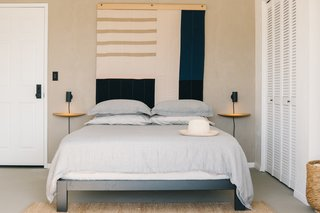 The master bedroom is a peaceful retreat against a backdrop of a Louise Gray wall tapestry, wall sconces from Rich Brilliant Willing, and Menu Fungi Shelves. Snowe linens outfit the bed, which boasts an Avocado mattress, and the Nest Rug is from Armadillo & Co.