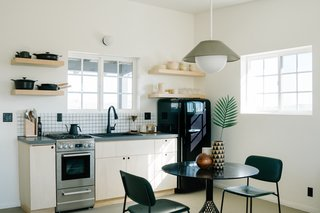 In the kitchen and dining area, the Akoya pendant by Rich Brilliant Willing hangs over a Bend Goods Bistro Table; the Hoist Sconce over the Signature Hardware kitchen sink and faucet is also by RBW. A Material Kitchen cookware set and Kinto coffee set outfits the kitchen, along with Neenineen ceramics and Snowe glassware. A SMEG fridge adds a retro touch.