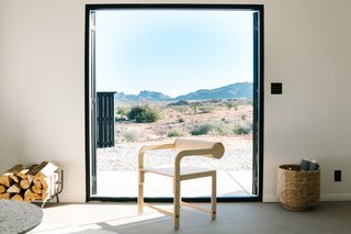 The living room frames the desert landscape through LaCantina doors. A WAKA WAKA Cylinder Back Arm Chair made from birch plywood adds warmth and character to the space.