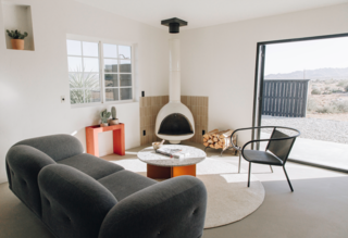 The living room provides a cozy gathering place anchored by a vintage fireplace from Urban Americana and Cle Tile backsplash. A circular Weave Rug pulls the space together.