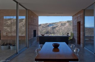 "Steel and glass combine with rammed earth to create a home that is both connected to the landscape, and distinctive from it. ""It can be really striking when the sun hits it, and there's a little glare,"" says Rick Joy. ""It's like any body of water in the desert."""