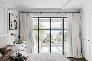 A guest bedroom offers floor-to-ceiling windows and a private balcony.