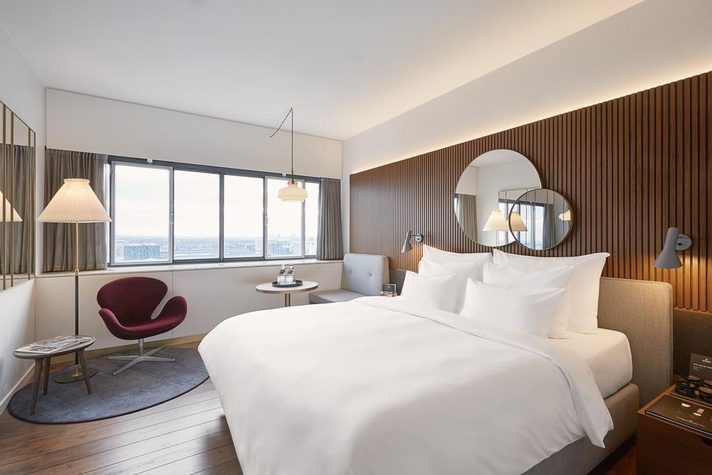 Bedroom, Rug, Chair, Dark Hardwood, Bed, Wall, Floor, and Night Stands  Best Bedroom Bed Floor Dark Hardwood Photos from Radisson Collection Royal Hotel, Copenhagen