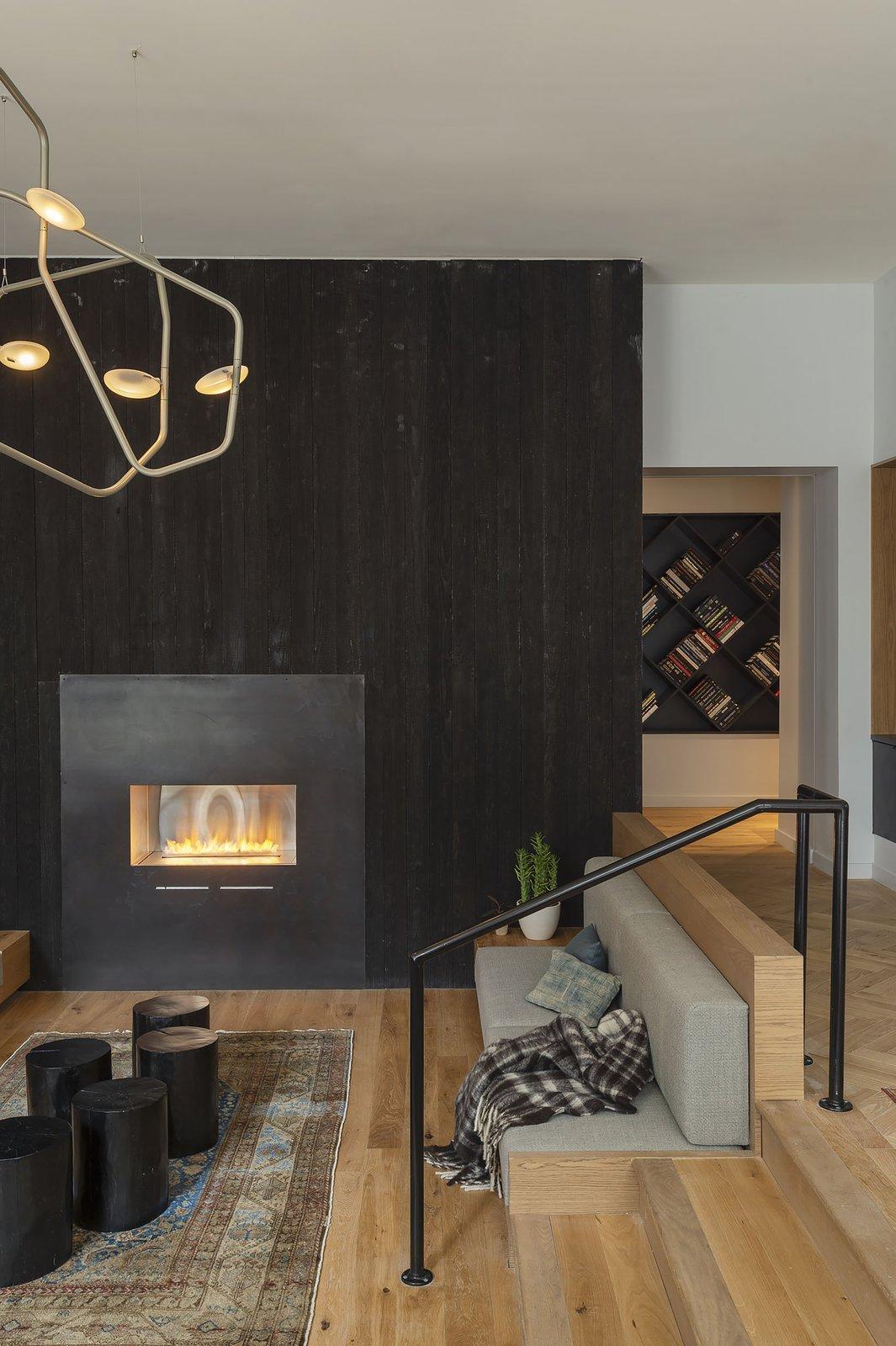 Living Room, Ribbon Fireplace, Bench, End Tables, Medium Hardwood Floor, Gas Burning Fireplace, Pendant Lighting, Light Hardwood Floor, and Rug Floor  ROOST Apartment Hotel
