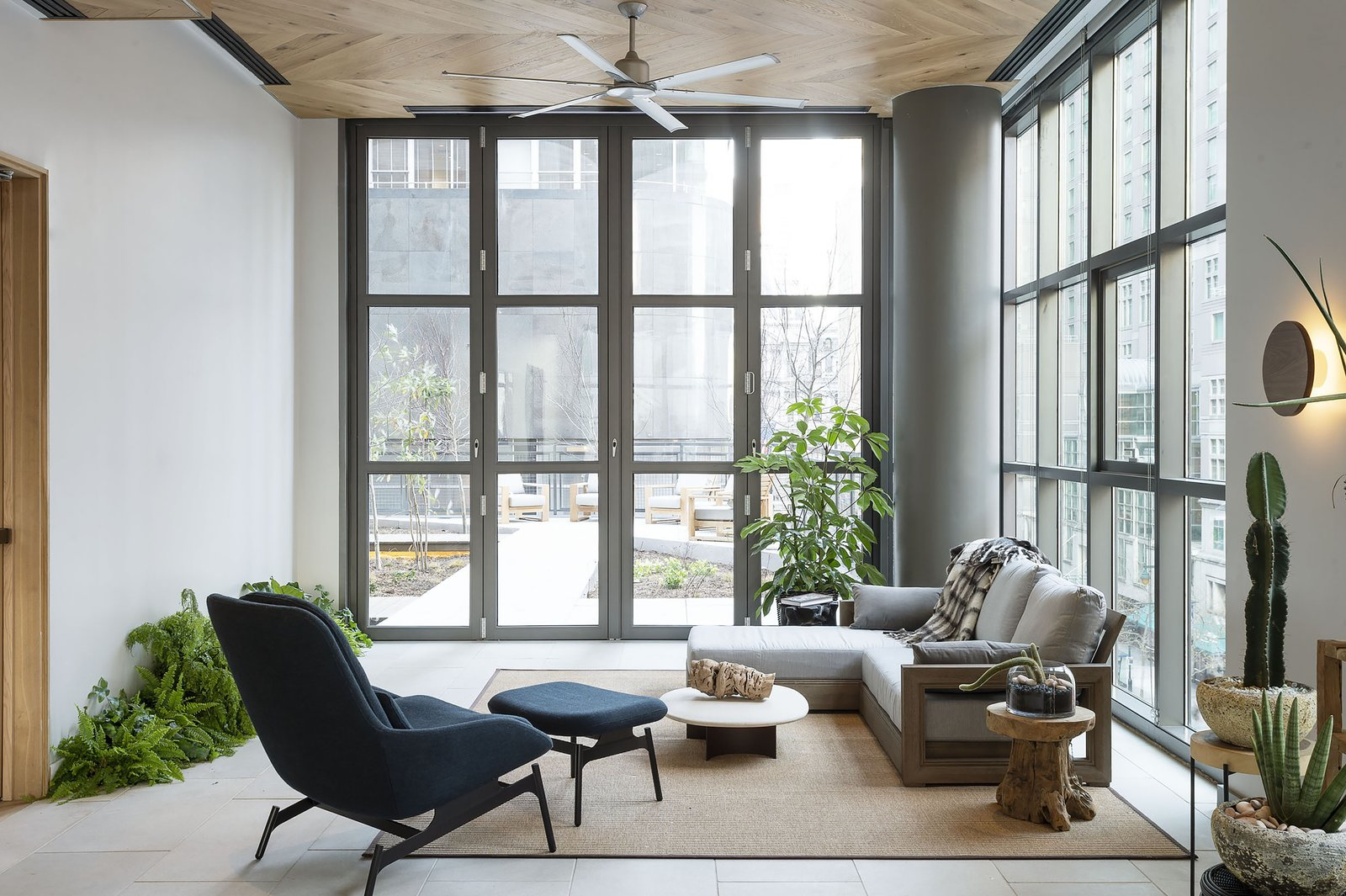 Living Room, Sectional, Wall Lighting, Chair, Coffee Tables, Porcelain Tile Floor, and Rug Floor  ROOST Apartment Hotel