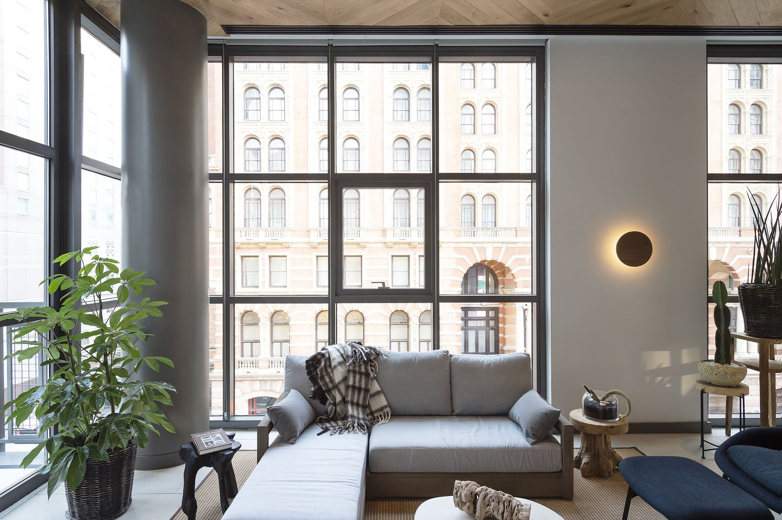Living Room, Wall Lighting, Coffee Tables, Rug Floor, End Tables, Porcelain Tile Floor, and Sectional  ROOST Apartment Hotel