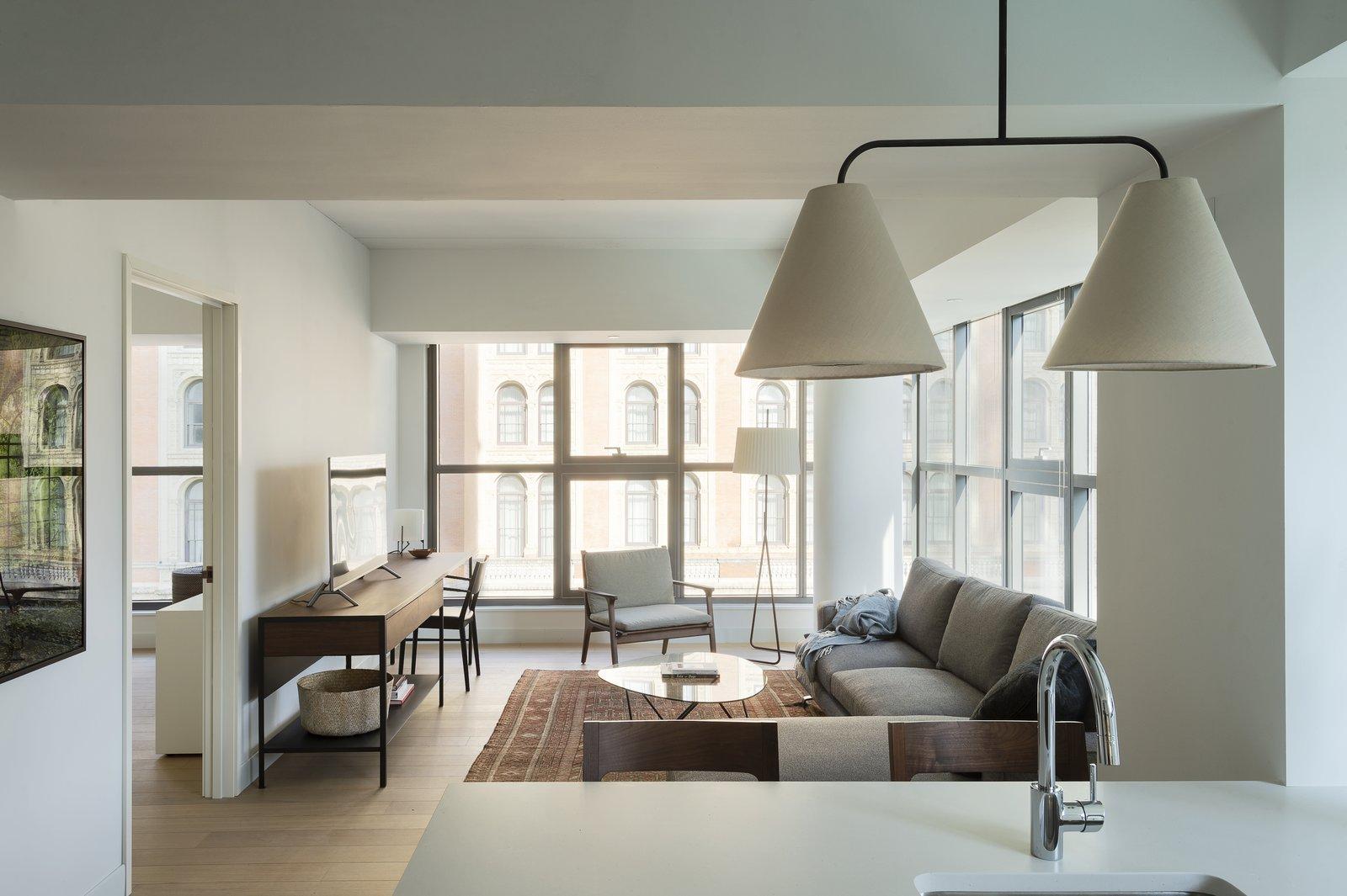 Living Room, Lamps, Console Tables, Rug Floor, Light Hardwood Floor, Sectional, Desk, Floor Lighting, Pendant Lighting, Coffee Tables, Table Lighting, and Chair  ROOST Apartment Hotel