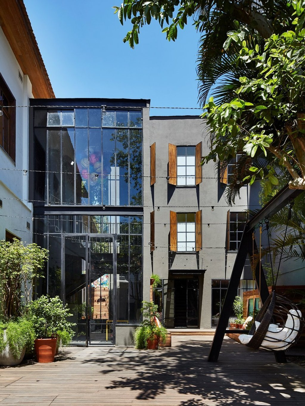 Outdoor, Decking Patio, Porch, Deck, Large Patio, Porch, Deck, Hanging Lighting, Raised Planters, Back Yard, and Trees  Dwell's Favorite Photos from Mama Shelter Rio De Janeiro