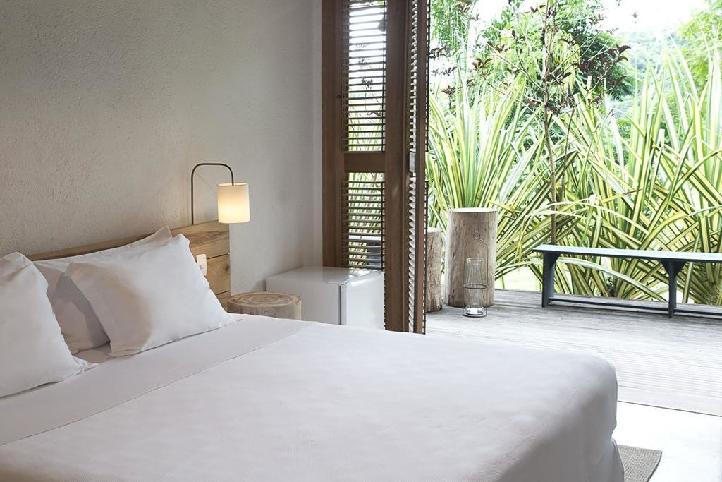 Bedroom, Bed, Night Stands, Wall Lighting, and Concrete Floor  Casa Mar Paraty