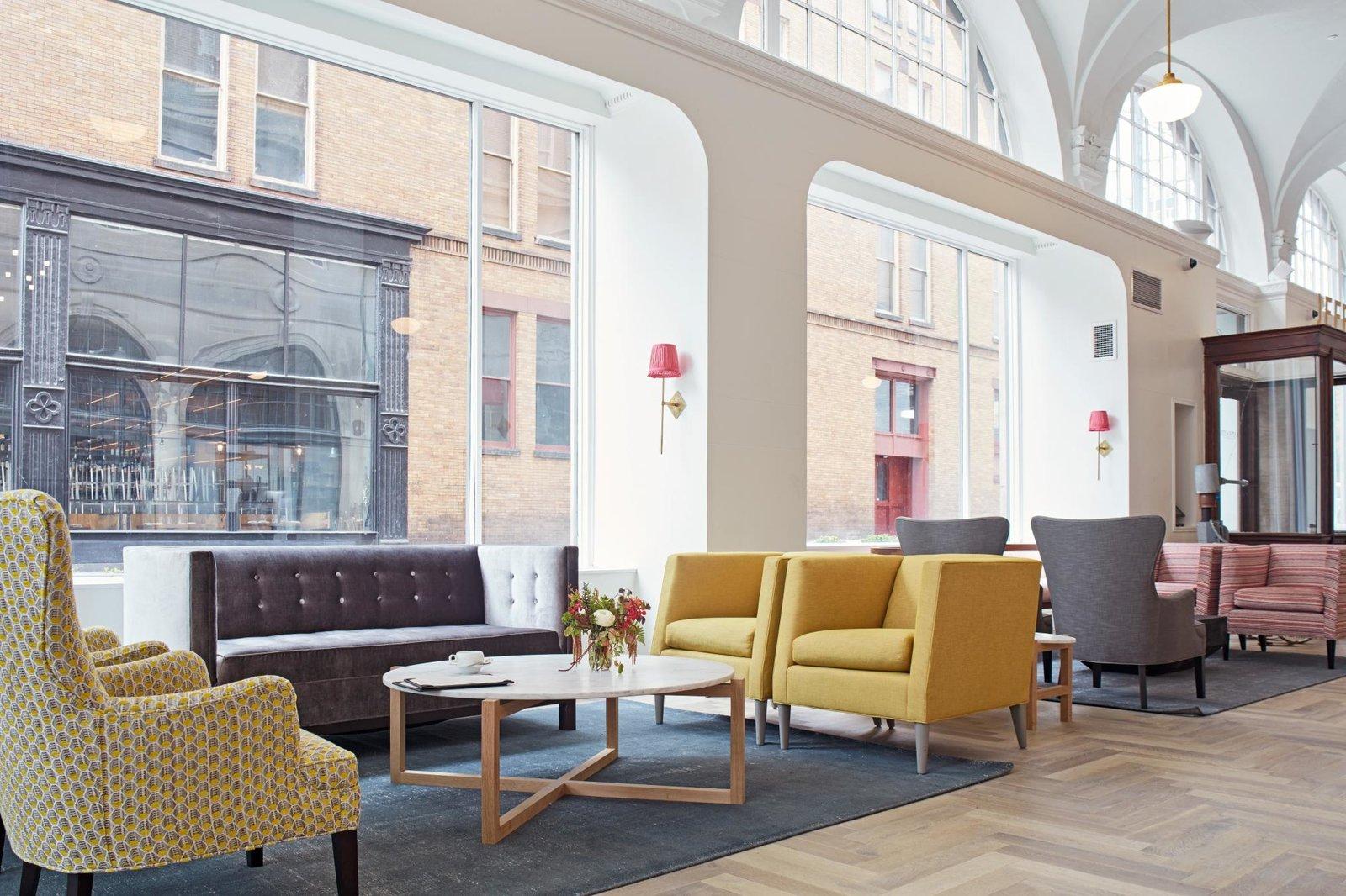 Living Room, Rug Floor, Chair, Sofa, Coffee Tables, Pendant Lighting, Medium Hardwood Floor, and Wall Lighting  Quirk Hotel